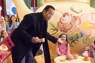 Sadly, the doll at the table has no way of smelling what the Rock is cooking.